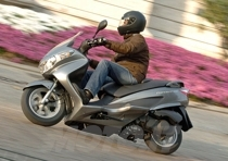 La posizione di guida è la classica da maxi scooter a ruota bassa, gambe avanti, sella bassa